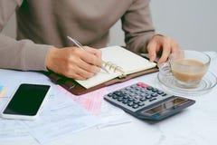 Passi l'uomo che fa le finanze e calcoli circa l'ufficio di costo a casa immagini stock