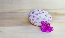 Passi l'uovo di Pasqua rosa di disegno su un fondo di legno Fotografia Stock Libera da Diritti