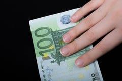 Passi la banconota dell'euro della tenuta 100 su un fondo nero Immagini Stock Libere da Diritti