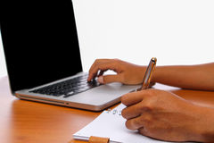 Passi la battitura a macchina del computer portatile a macchina sulle tavole di legno d'annata Fotografie Stock