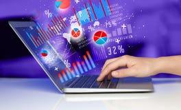 Passi la battitura a macchina sul computer portatile moderno del computer portatile con le icone del grafico Fotografia Stock