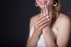 Passi la bella sposa della ragazza in vestito da sposa bianco con i chiodi acrilici e modello e cristalli di rocca delicati Fotografia Stock Libera da Diritti