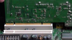 Passi la carta del PCI dell'inserzione nella scanalatura della scheda madre sul desktop computer video d archivio
