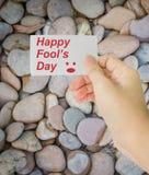 Passi la carta della tenuta con il giorno dello sciocco felice di parola Immagini Stock Libere da Diritti