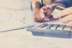 Passi la carta di credito della tenuta che calcola le sue spese mensili con il calendario di termine Immagini Stock