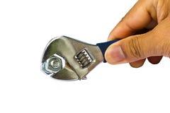 Passi la chiave della stretta per stringere la noce su bianco Fotografia Stock