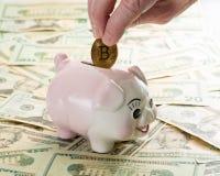 Passi la collocazione della moneta del bitcoin nel porcellino salvadanaio Fotografia Stock Libera da Diritti