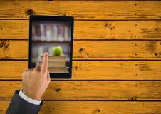 Passi la compressa commovente che mostra il mucchio del libro con la mela sulla tavola gialla Immagini Stock Libere da Diritti
