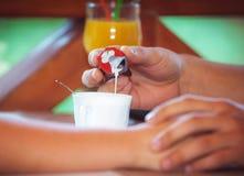 Passi la crema di versamento in una tazza di caffè Fotografie Stock Libere da Diritti