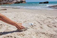 Passi la donna che prende il lavaggio delle bottiglie di plastica sulla spiaggia, concetto volontario Ecologia e concetto di gior fotografia stock libera da diritti