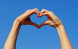 Passi la fabbricazione del segno dell'amore con i precedenti del cielo blu Fotografia Stock
