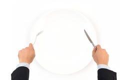 Passi la forcella ed il coltello della tenuta con il piatto bianco Fotografia Stock