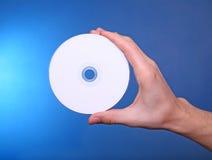Passi la holding che mostra a dvd cd il disco blu del raggio Fotografie Stock