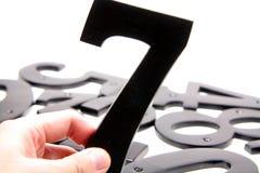 Passi la holding il numero 7 fotografia stock libera da diritti
