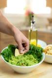 Passi la immersione del chip in una ciotola deliziosa fresca di guacamole fatto a mano con gli ingredienti vicini Immagine Stock Libera da Diritti