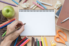 Passi la matita della tenuta con i rifornimenti di scuola ed il Libro Bianco Immagine Stock