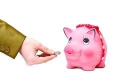 La mano dà la moneta a moneybox Fotografie Stock