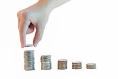 Passi la moneta in dita e nelle pile di fila di moneta per il concetto di risparmio Fotografia Stock