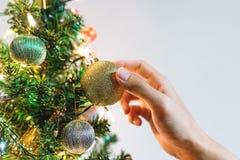 Passi la palla dorata scintillante d'attaccatura di Natale sull'albero di Natale per la decorazione nella festa Fotografie Stock