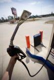 Passi la pompa di gas della holding con soldi in ugello Immagine Stock Libera da Diritti