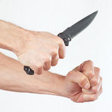 Passi la posizione all'attacco con un coltello di esercito su fondo bianco Immagini Stock