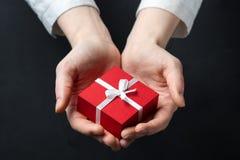 Passi la scatola della tenuta per un regalo isolato sul nero immagini stock