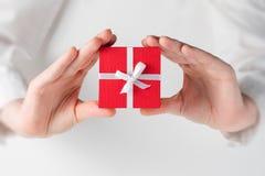Passi la scatola della tenuta per un regalo su bianco immagine stock libera da diritti