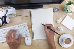 Passi la scrittura della matita di uso sulla nota e sugli oggetti business del Libro Bianco immagine stock libera da diritti