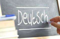 Passi la scrittura su una lavagna in una classe di lingua con la parola & il x22; German& x22; scritto su  Immagini Stock Libere da Diritti