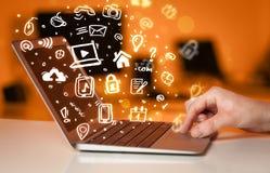 Passi la scrittura sul computer portatile con le icone ed i simboli di media Immagine Stock