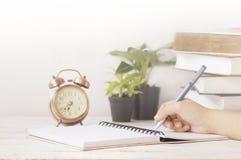 Passi la scrittura sulla carta per appunti alla tavola di funzionamento con la sveglia Fotografia Stock Libera da Diritti