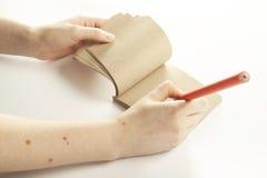 Passi la scrittura in taccuino fatto da documento riciclato Fotografia Stock