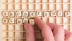 Passi la spiegazione dell'alfabeto in dadi di legno su una griglia stock footage