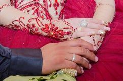 Passi la sposa e lo sposo orientali in un vestito rosso con le fedi nuziali sul mazzo di nozze Immagine Stock Libera da Diritti