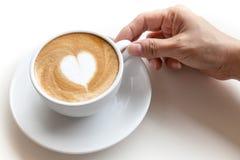 Passi la tazza di caffè della tenuta di forma del cuore di arte del latte su backgr bianco fotografie stock