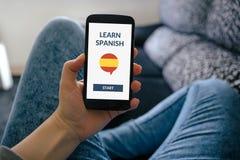 Passi la tenuta che lo Smart Phone con online impara il concetto spagnolo su Sc Fotografie Stock
