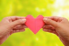 Passi la tenuta degli origami rossi della carta del cuore sulle sedere naturali verdi vaghe Immagine Stock