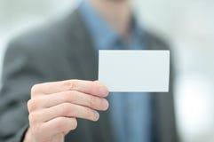 Passi la tenuta del biglietto da visita bianco su fondo vago rosso Fotografie Stock Libere da Diritti
