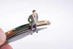 Passi la tenuta del coltello di tasca vicino ad una figura Immagini Stock Libere da Diritti