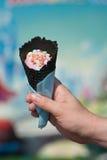 Passi la tenuta del cono nero della cialda con il gelato rosa su un fondo colorato luminoso Fotografia Stock Libera da Diritti