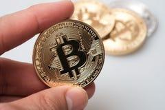 Passi la tenuta del cryptocurrency dorato del bitcoin su fondo bianco Immagine Stock