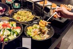 Passi la tenuta del cucchiaio inossidabile d'argento con frutta mista e il seafo immagine stock