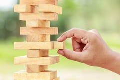 Passi la tenuta del gioco di legno dei blocchi (jenga) su backgroun verde vago fotografia stock libera da diritti