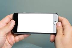 Passi la tenuta del iPhone 6 di Apple con lo schermo in bianco Immagine Stock Libera da Diritti