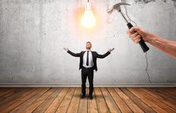 Passi la tenuta del martello che va rompere la lampadina d'ardore sopra businessman& x27; testa di s Immagini Stock