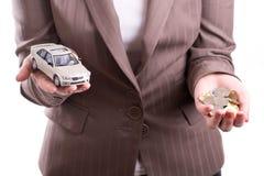 Passi la tenuta del modello dell'automobile e delle monete Fotografie Stock
