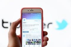 Passi la tenuta del telefono cellulare ed usando la rete sociale Twitter Immagini Stock