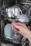 Passi la tenuta del vetro pulito su un fondo della lavastoviglie Immagini Stock Libere da Diritti