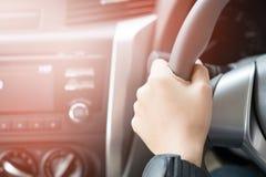 Passi la tenuta del volante del ` s dell'automobile fotografia stock