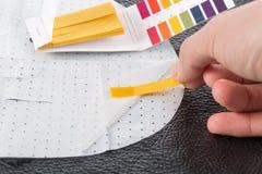 Passi la tenuta dell'indicatore di pH che confronta il colore alla scala Immagini Stock